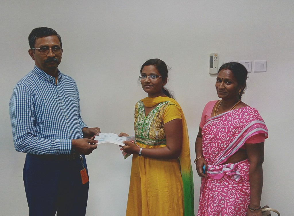 The Trustee has handed over an educational aid cheque to Sournabagavathi for her B.Com. first-year studies.